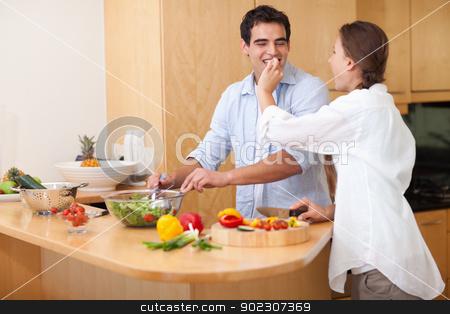 Woman feeding her husband stock photo, Woman feeding her husband while cooking by Wavebreak Media
