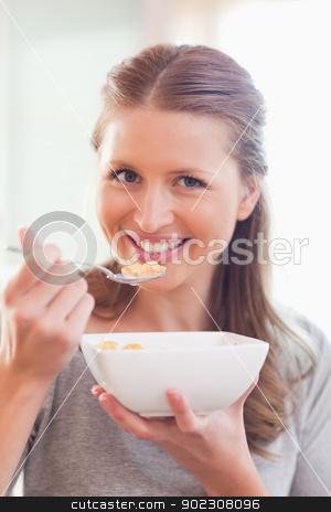 Close up of smiling woman having breakfast stock photo, Close up of smiling young woman having breakfast by Wavebreak Media