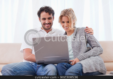 Couple using a laptop stock photo, Couple using a laptop in their living room by Wavebreak Media