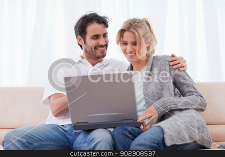 Couple using a notebook stock photo, Couple using a notebook in their living room by Wavebreak Media