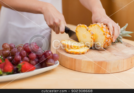 Close up of a pineapple being sliced stock photo, Close up of a pineapple being sliced in a kitchen by Wavebreak Media