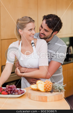 Portrait of a couple eating fruits stock photo, Portrait of a couple eating fruits in their kitchen by Wavebreak Media