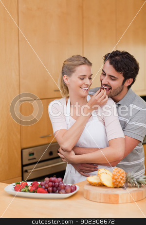Portrait of a young couple eating fruits stock photo, Portrait of a young couple eating fruits in their kitchen by Wavebreak Media