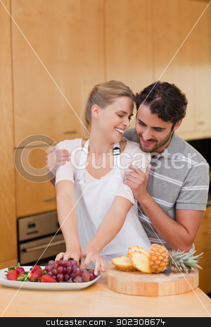 Portrait of a lovely couple eating fruits stock photo, Portrait of a lovely couple eating fruits in their kitchen by Wavebreak Media