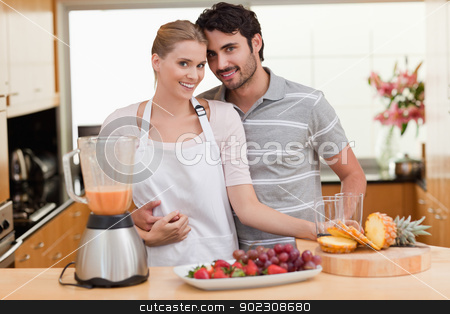 Couple making fresh fruits juice stock photo, Couple making fresh fruits juice in their kitchen by Wavebreak Media