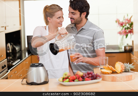 Young couple making fresh fruits juice stock photo, Young couple making fresh fruits juice in their kitchen by Wavebreak Media