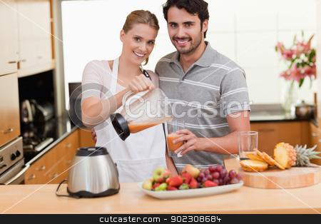 Young couple making fruits juice stock photo, Young couple making fruits juice in their kitchen by Wavebreak Media