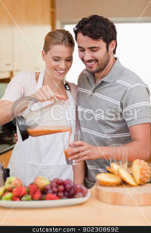 Portrait of a young couple drinking fruits juice stock photo, Portrait of a young couple drinking fruits juice in their kitchen by Wavebreak Media
