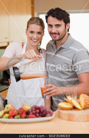 Portrait of a smiling couple drinking fruits juice stock photo, Portrait of a smiling couple drinking fruits juice in their kitchen by Wavebreak Media