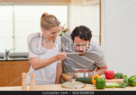 Couple preparing a sauce stock photo, Couple preparing a sauce in their kitchen by Wavebreak Media