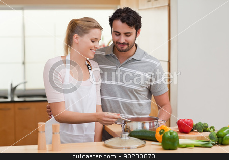 Lovely couple preparing a sauce stock photo, Lovely couple preparing a sauce in their kitchen by Wavebreak Media