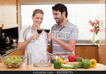 Couple drinking a glass of wine stock photo, Couple drinking a glass of wine in their kitchen by Wavebreak Media