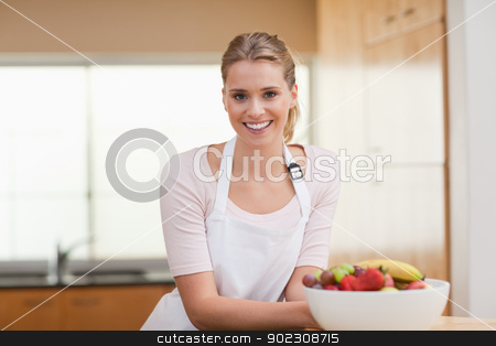 Woman posing with a fruit basket stock photo, Woman posing with a fruit basket in her kitchen by Wavebreak Media