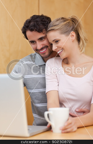 Portrait of a couple using a laptop while having tea stock photo, Portrait of a couple using a laptop while having tea in their kitchen by Wavebreak Media