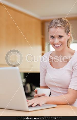 Portrait of a woman using a laptop while drinking coffee stock photo, Portrait of a woman using a laptop while drinking coffee in her kitchen by Wavebreak Media