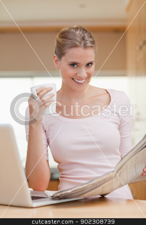 Portrait of a woman reading a newspaper while having coffee stock photo, Portrait of a woman reading a newspaper while having coffee in her kitchen by Wavebreak Media