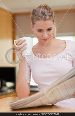 Portrait of a young woman reading the news while having coffee stock photo, Portrait of a young woman reading the news while having coffee in her kitchen by Wavebreak Media