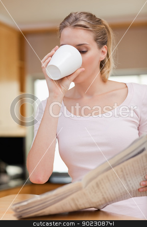 Portrait of a young woman reading the news while having tea stock photo, Portrait of a young woman reading the news while having tea in her kitchen by Wavebreak Media