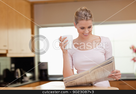 Woman reading the news while having tea stock photo, Woman reading the news while having tea in her kitchen by Wavebreak Media