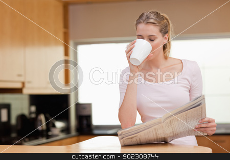 Woman reading the news while having coffee stock photo, Woman reading the news while having coffee in her kitchen by Wavebreak Media