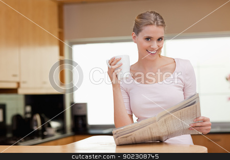 Young woman reading the news while having coffee stock photo, Young woman reading the news while having coffee in her kitchen by Wavebreak Media