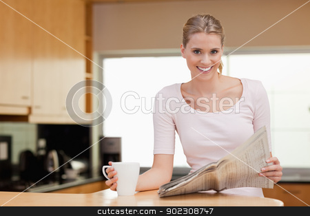 Smiling woman reading the news while having tea stock photo, Smiling woman reading the news while having tea in her kitchen by Wavebreak Media