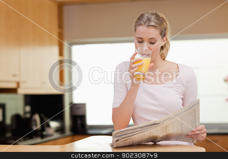 Young woman reading the news while drinking orange juice stock photo, Young woman reading the news while drinking orange juice in her kitchen by Wavebreak Media