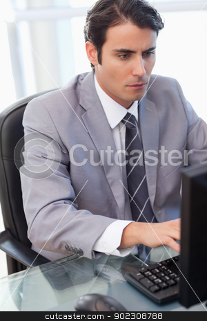 Portrait of a focused businessman working with a computer stock photo, Portrait of a focused businessman working with a computer in his office by Wavebreak Media