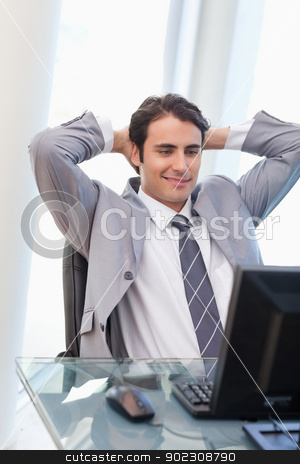 Portrait of a relaxed businessman working with a computer stock photo, Portrait of a relaxed businessman working with a computer in his office by Wavebreak Media