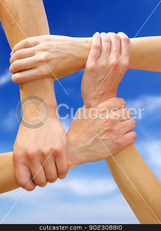 linked hands stock photo, Linked hands on a sky background symbolizing teamwork and friendship by Vitaliy Pakhnyushchyy