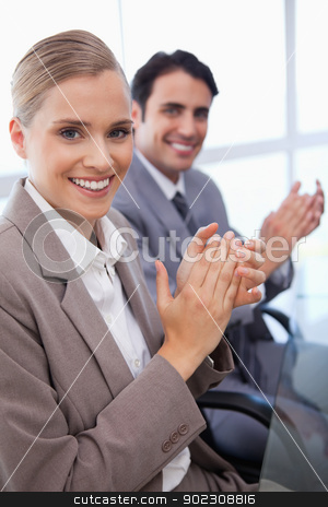 Portrait of a smiling business team applauding stock photo, Portrait of a smiling business team applauding in a meeting room by Wavebreak Media