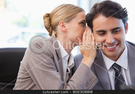 Young businesswoman whispering something to her colleague stock photo, Young businesswoman whispering something to her colleague in a meeting room by Wavebreak Media
