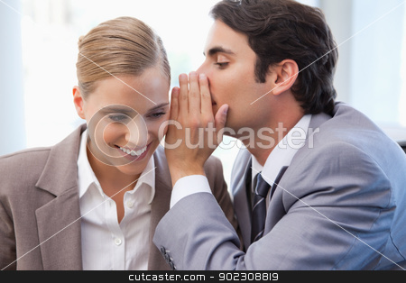Businessman whispering something to his colleague stock photo, Businessman whispering something to his colleague in a meeting room by Wavebreak Media