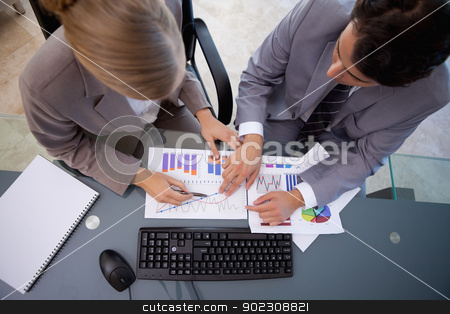 Serisous business team studying statistics stock photo, Serisous business team studying statistics in a meeting room by Wavebreak Media