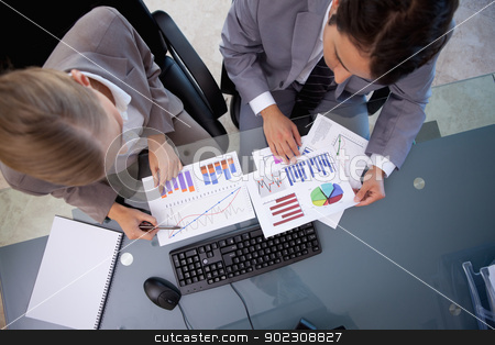 Business team looking at statistics stock photo, Business team looking at statistics in a meeting room by Wavebreak Media