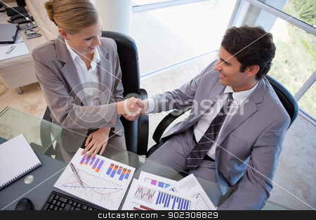 Business people agreeing on a deal stock photo, Business people agreeing on a deal in a meeting room by Wavebreak Media
