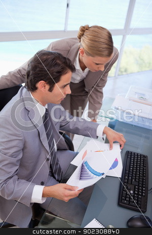 Portrait of a manager and his secretary looking at a graph stock photo, Portrait of a manager and his secretary looking at a graph in his office by Wavebreak Media