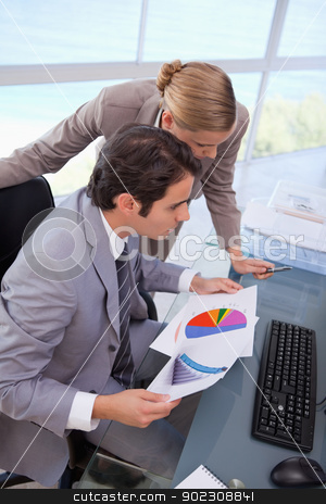 Portrait of a business team looking at a graph stock photo, Portrait of a business team looking at a graph in an office by Wavebreak Media