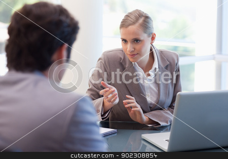 Professional businesswoman receiving a customer stock photo, Professional businesswoman receiving a customer in her office by Wavebreak Media