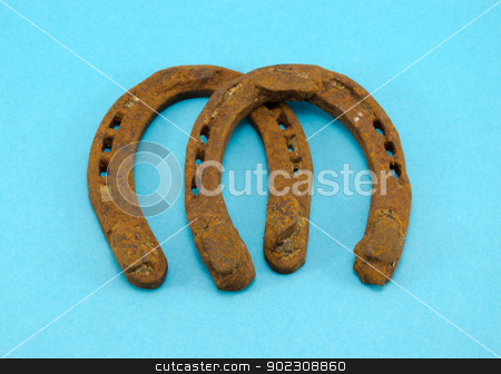 retro rusty pair of horseshoes on blue background  stock photo, retro rusty pair of horseshoes on blue background.  by sauletas