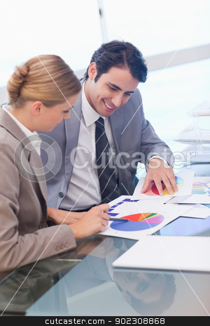 Portrait of smiling business people studying statistics stock photo, Portrait of smiling business people studying statistics in a meeting room by Wavebreak Media