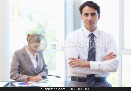 Businessman posing while his colleague is working stock photo, Businessman posing while his colleague is working in a meeting room by Wavebreak Media
