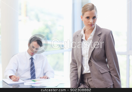 Businesswoman posing while her colleague is working stock photo, Businesswoman posing while her colleague is working in a meeting room by Wavebreak Media