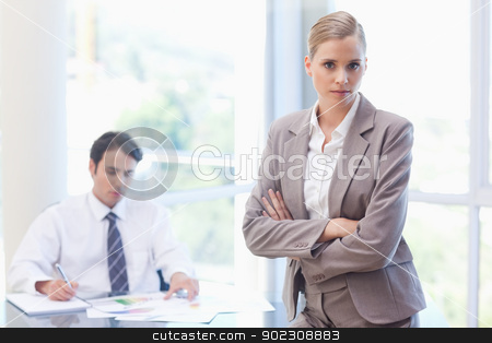 Serious businesswoman posing while her colleague is working stock photo, Serious businesswoman posing while her colleague is working in a meeting room by Wavebreak Media