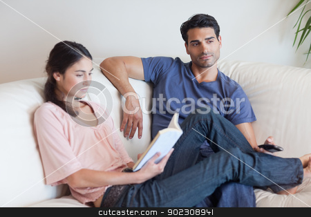 Woman reading a book while her boyfriend is watching television stock photo, Woman reading a book while her boyfriend is watching television in their living room by Wavebreak Media