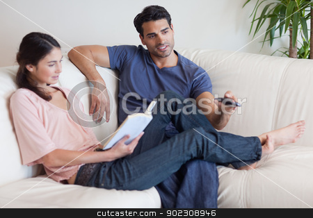 Woman reading a book while her fiance is watching television stock photo, Woman reading a book while her fiance is watching television in their living room by Wavebreak Media