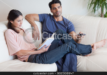 Woman reading a book while her fiance is watching TV stock photo, Woman reading a book while her fiance is watching TV in their living room by Wavebreak Media