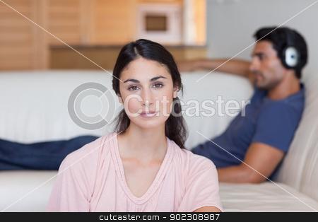 Woman posing while her boyfriend is listening to music stock photo, Woman posing while her boyfriend is listening to music in their living room by Wavebreak Media
