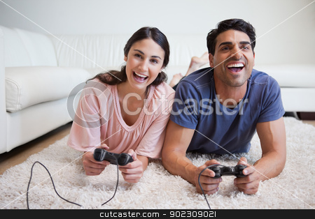 Playful couple playing video games stock photo, Playful couple playing video games in their living room by Wavebreak Media
