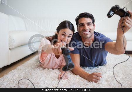 Playful young couple playing video games stock photo, Playful young couple playing video games in their living room by Wavebreak Media